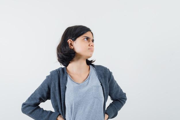 Jong meisje in lichtgrijs t-shirt en donkergrijze hoodie met rits aan de voorkant, hand in hand op de taille, wegkijkend en schattig,