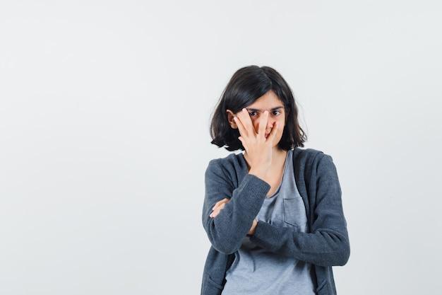 Jong meisje in lichtgrijs t-shirt en donkergrijze hoodie met ritssluiting die een deel van het gezicht bedekt met de hand, door de vingers kijkt en er schattig uitziet