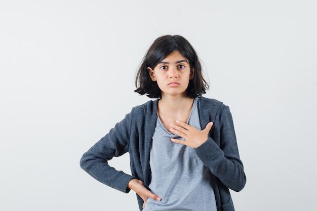 Jong meisje in lichtgrijs t-shirt en donkergrijze hoodie met ritssluiting die hand op de taille houdt, zichzelf wijst en er schattig uitziet