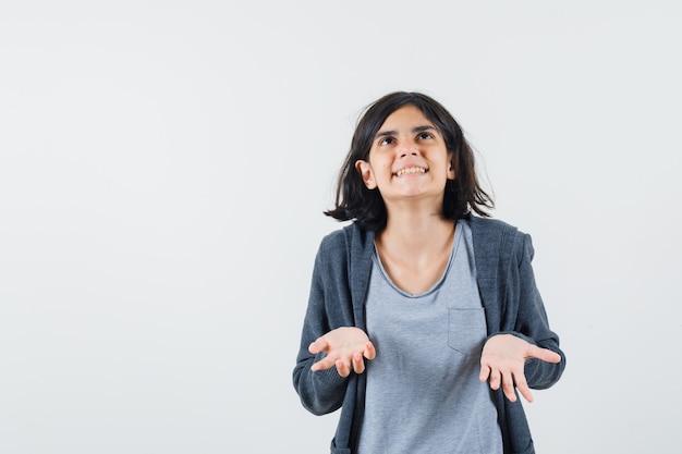 Jong meisje in lichtgrijs t-shirt en donkergrijze hoodie met ritssluiting die hand uitrekt als iets probeert vast te houden en naar boven kijkt en opgewonden kijkt