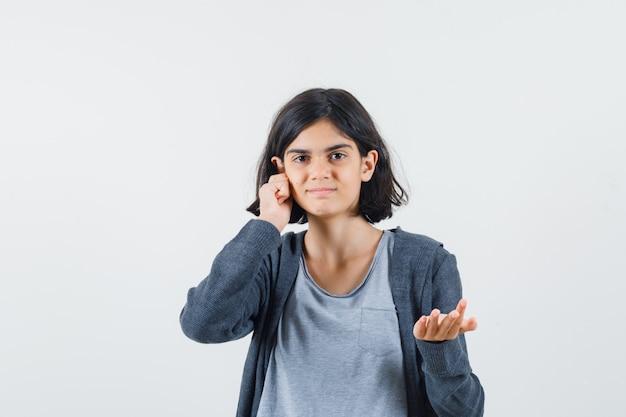 Jong meisje in lichtgrijs t-shirt en donkergrijze hoodie met ritssluiting die hand uitstrekt naar de camera als iets ontvangt en de hand op het oor legt en er schattig uitziet,