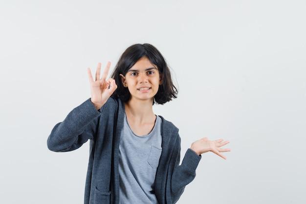 Jong meisje in lichtgrijs t-shirt en donkergrijze hoodie met ritssluiting die ok teken toont en hand uitstrekt en er schattig uitziet