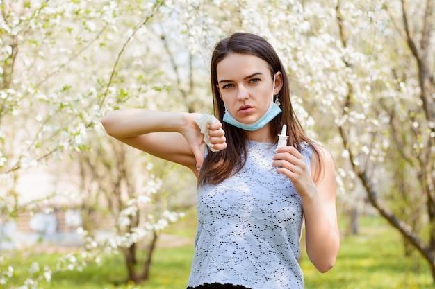 Jong meisje in medisch masker die duimen tonen die zich in bloeiende tuin bevinden en nevel voor lopende neus houden