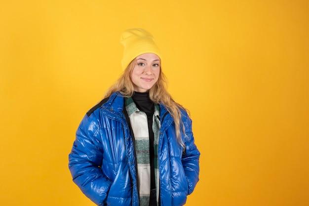 Jong meisje in moderne straatkleren op gele achtergrond