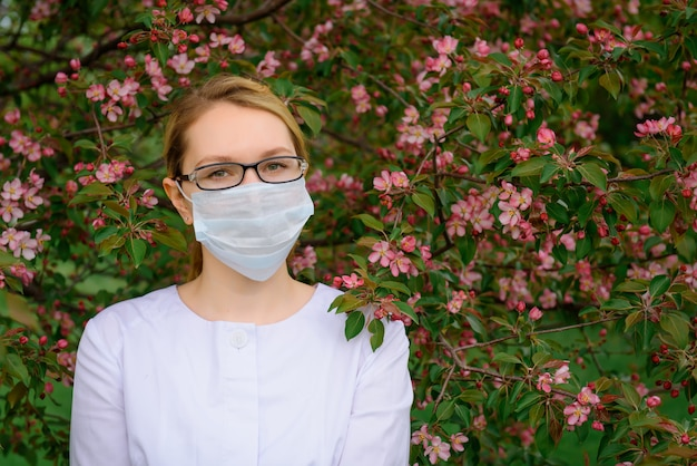 Jong meisje in oogglazen en medisch masker door boom te bloeien. portret van mooie goed verzorgde vrouwelijke arts in de zomer groen park.