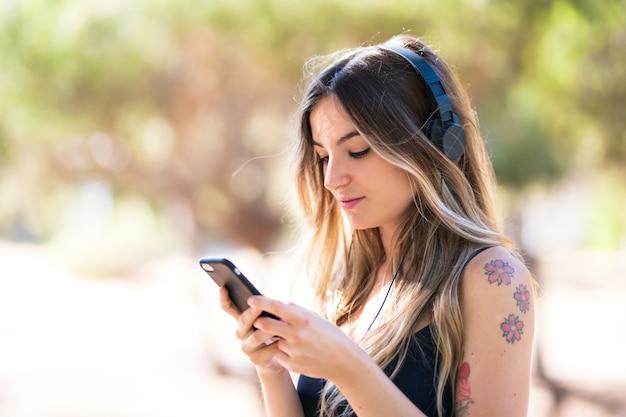 Jong meisje in openlucht in een park dat aan muziek met mobiel luistert