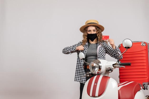 Jong meisje in panama met een masker met een kaartje in de buurt van een rode bromfiets