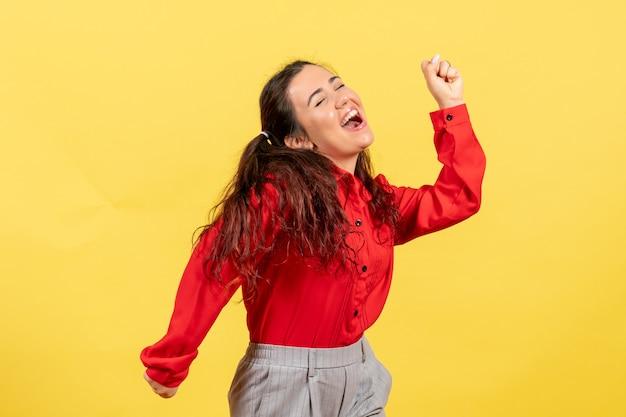 Jong meisje in rode blouse dansen op geel
