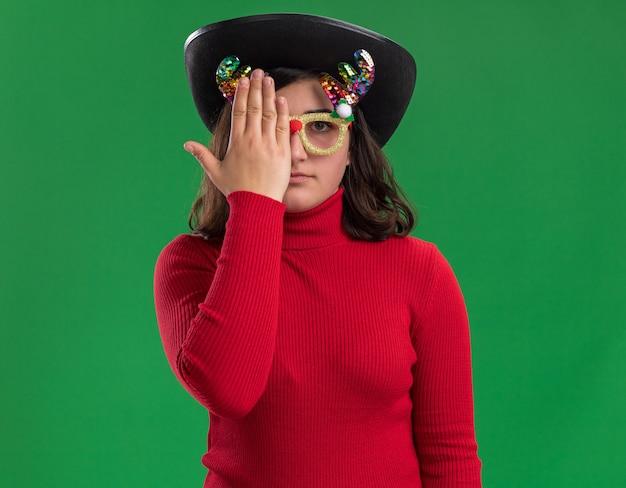 Jong meisje in rode sweater die grappige glazen en zwarte hoed dragen die één oog met hand behandelen