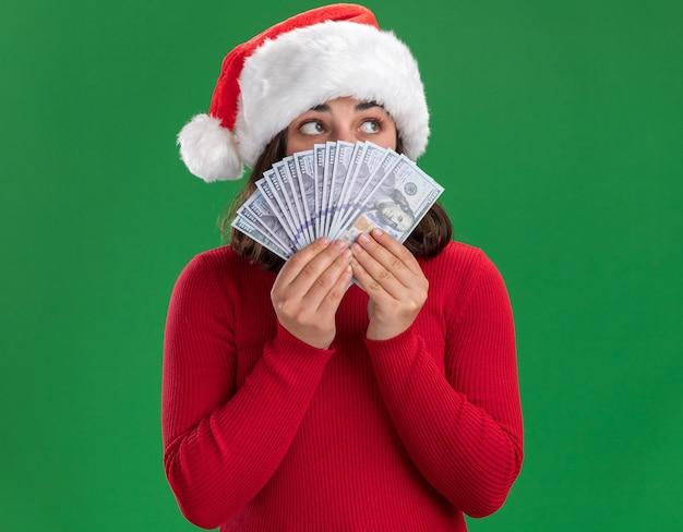Jong meisje in rode trui en kerstmuts die gezicht bedekt met geld, opzij kijkend, bezorgd met contant geld dat over groene achtergrond staat