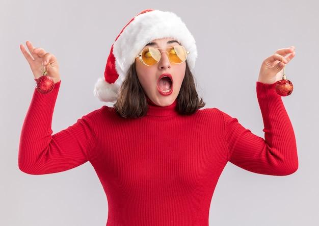 Jong meisje in rode trui en kerstmuts met bril bedrijf kerstballen kijken opzij verrast staande op witte achtergrond