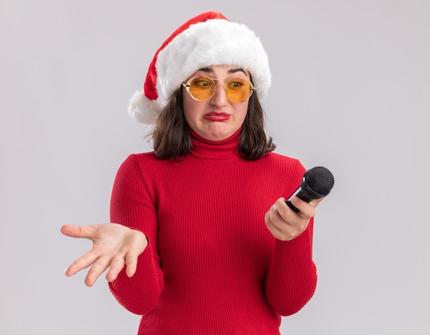 Jong meisje in rode trui en kerstmuts met bril houden microfoon kijken met verwarren uitdrukking met arm uit staande op witte achtergrond