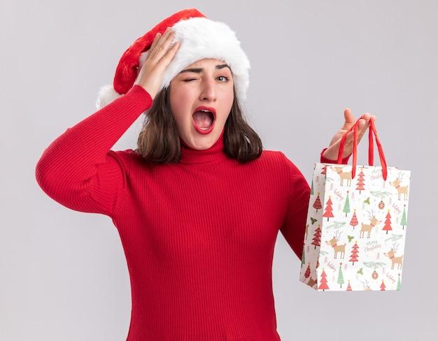 Jong meisje in rode trui en kerstmuts met kleurrijke papieren zak met kerstcadeaus verrast staande over witte muur