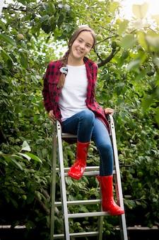 Jong meisje in rode wellington laarzen zittend op trapladder in de tuin