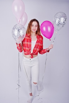 Jong meisje in rood geruit hemd en witte broek met ballonnen
