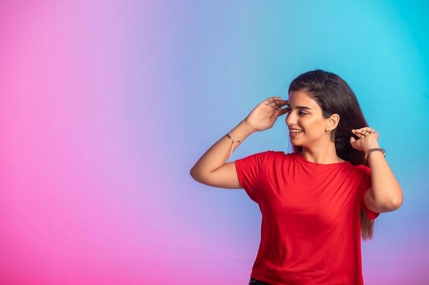 Jong meisje in rood overhemd in het gieten.
