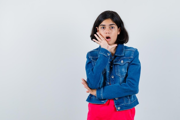 Jong meisje in rood t-shirt en spijkerjasje dat handen in de buurt van mond zet als iemand belt en nieuwsgierig kijkt, vooraanzicht.