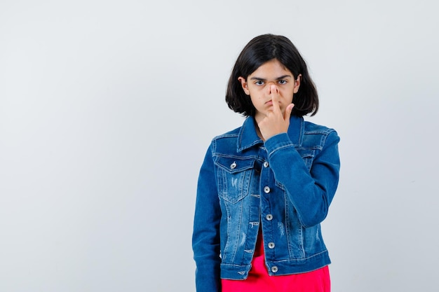 Jong meisje in rood t-shirt en spijkerjasje dat wijsvinger op de mond zet en er serieus uitziet, vooraanzicht.
