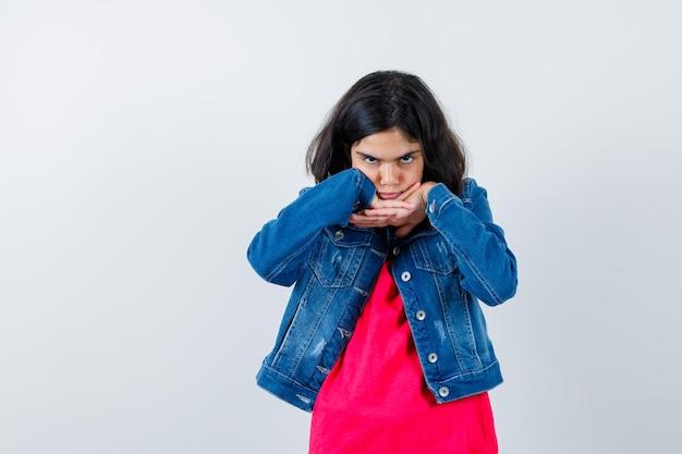 Jong meisje in rood t-shirt en spijkerjasje hand in hand onder de kin en ziet er serieus uit, vooraanzicht.