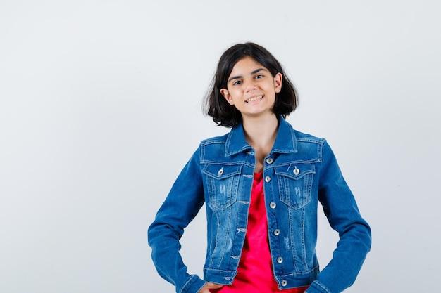 Jong meisje in rood t-shirt en spijkerjasje hand in hand op taille, glimlachend en optimistisch, vooraanzicht.