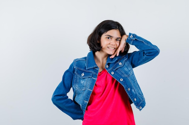 Jong meisje in rood t-shirt en spijkerjasje leunend op de handpalm terwijl ze de hand op de taille houdt en er gelukkig uitziet, vooraanzicht.