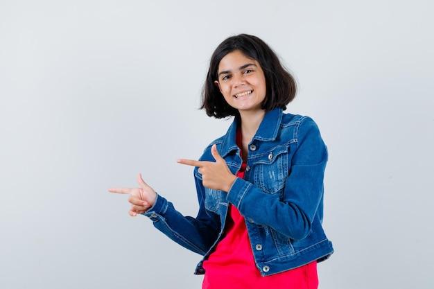Jong meisje in rood t-shirt en spijkerjasje naar links wijzend met wijsvingers en er gelukkig uitzien, vooraanzicht.