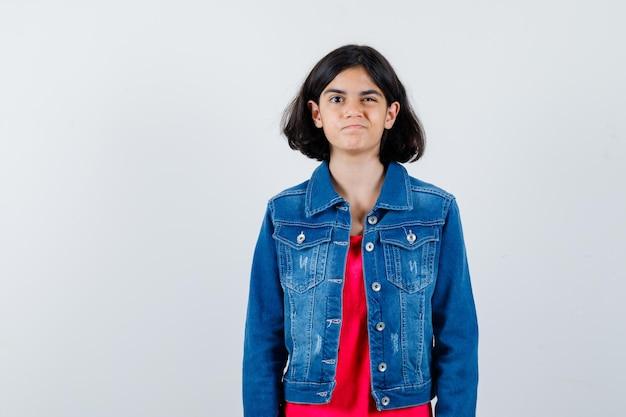 Jong meisje in rood t-shirt en spijkerjasje staat rechtop, knipoogt en poseert voor de camera en ziet er schattig uit
