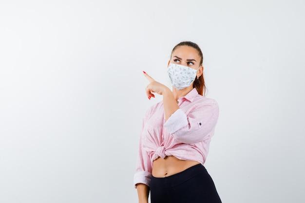 Jong meisje in roze blouse, zwarte broek, masker naar links wijzend met wijsvinger, wegkijkend en verleidelijk, vooraanzicht.