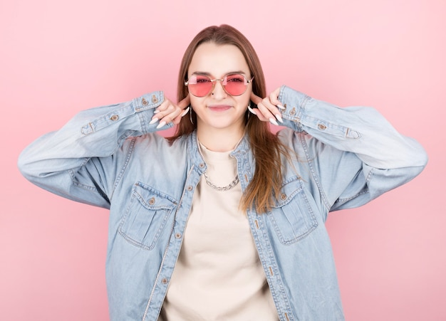 Jong meisje in roze bril, denimoverhemd, met een ketting om haar hals, die haar oren bedekt