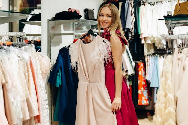 Jong meisje in roze in de winkel presenteert een mooie, nieuwe jurk