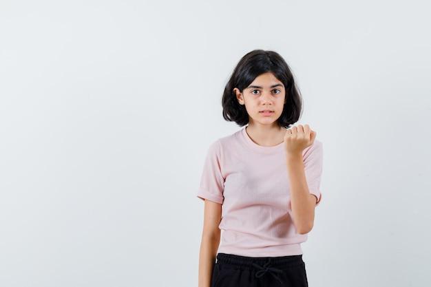 Jong meisje in roze t-shirt en zwarte broek balde vuist en ziet er schattig uit