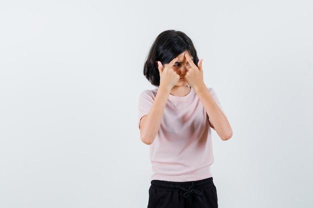 Jong meisje in roze t-shirt en zwarte broek die een puistje knalt en ernstig kijkt