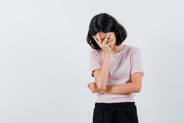 Jong meisje in roze t-shirt en zwarte broek die gezicht met hand bedekken en uitgeput kijkt