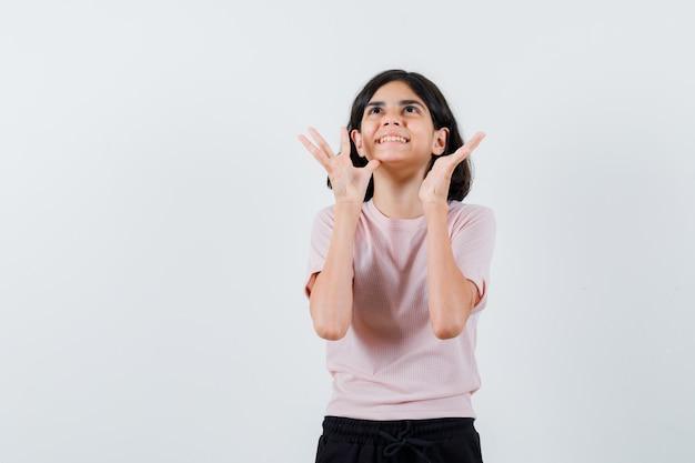Jong meisje in roze t-shirt en zwarte broek die handen opheft als iets probeert vast te houden en gelukkig kijkt