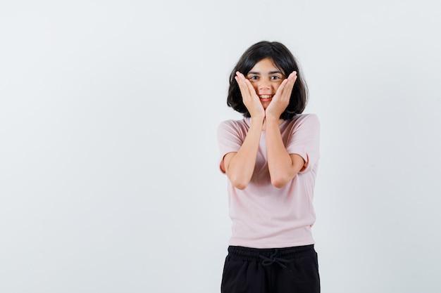 Jong meisje in roze t-shirt en zwarte broek hand in hand op de wangen en ziet er schattig uit