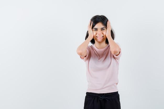 Jong meisje in roze t-shirt en zwarte broek hand in hand op het hoofd en op zoek gelukkig