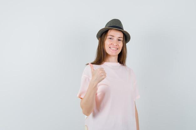 Jong meisje in roze t-shirt, hoed die duim toont en vrolijk, vooraanzicht kijkt.