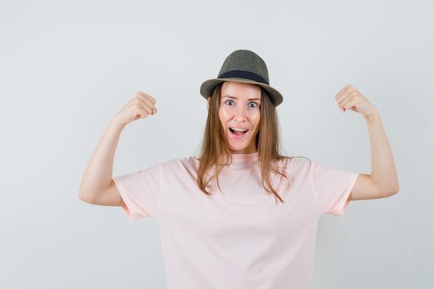 Jong meisje in roze t-shirt, hoed die winnaargebaar toont en gelukkig, vooraanzicht kijkt.