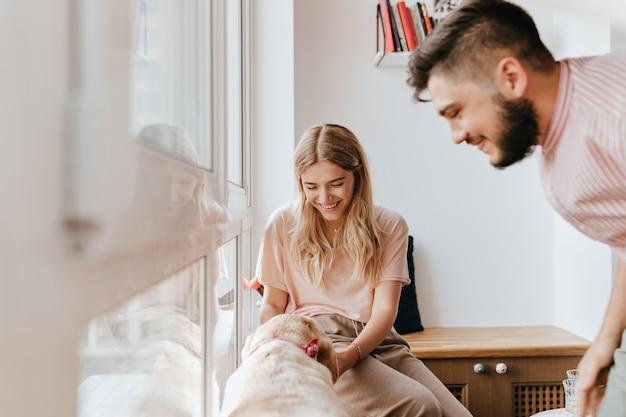 Jong meisje in roze t-shirt speelt met hond terwijl haar vriendje ernaar kijkt met een glimlach.