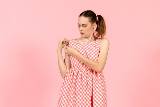 Jong meisje in schattige lichte jurk controleren op roze