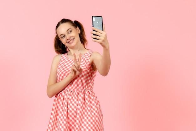 Jong meisje in schattige lichte jurk selfie te nemen op roze