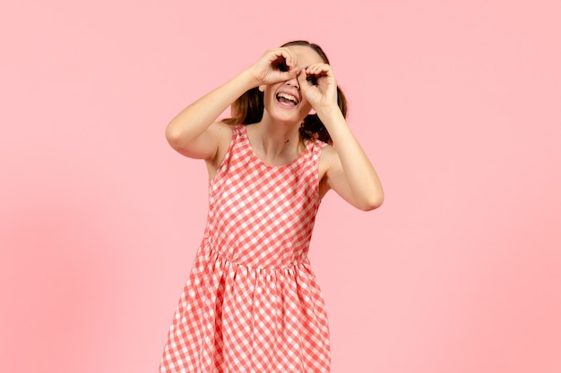 Jong meisje in schattige roze jurk kijkt door haar vingers op roze
