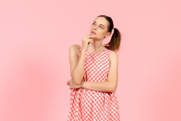 Jong meisje in schattige roze jurk met denken expressie op roze