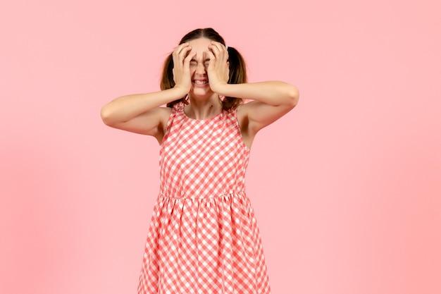 Jong meisje in schattige roze jurk met een boos gezicht op roze