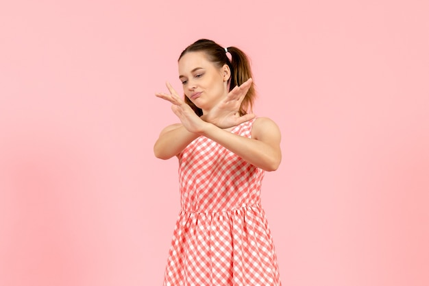 Jong meisje in schattige roze jurk met ontevreden gezicht op roze