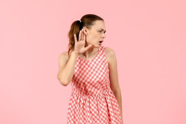 Jong meisje in schattige roze jurk nauw luisteren op roze