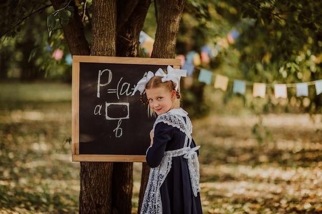 Jong meisje in schooluniform met witte bogen die op een raad in een park schrijven