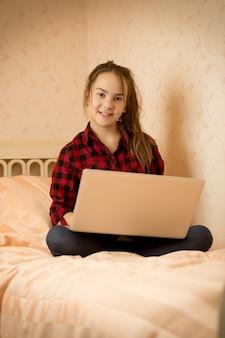 Jong meisje in shirt zittend op bed in slaapkamer met laptop with