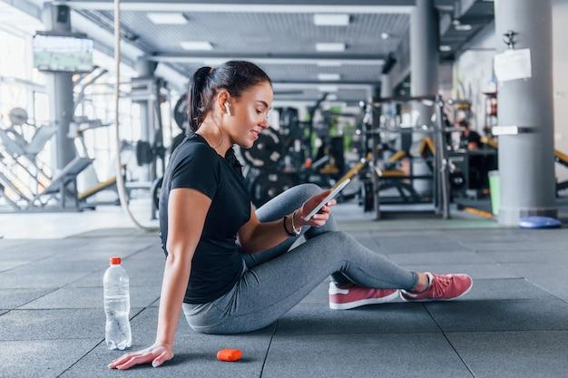 Jong meisje in sportieve kleding die een pauze neemt met eten en water is overdag in de sportschool.