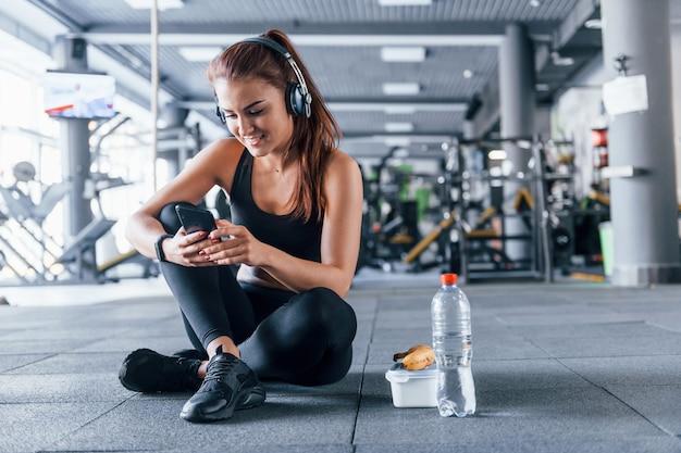 Jong meisje in sportieve kleding en koptelefoon zittend in de sportschool overdag met eten.